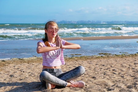 The girl practices yoga by the sea. Exercise gymnastics in the fresh air by the sea.
