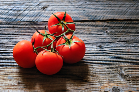 Wooden background with red washed tomatoes in left side. Copy space. Top view.