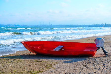 Summer Vacations. The red kayak is parked on the sandy beach on a sunny day, waiting for people to paddle out to sea.