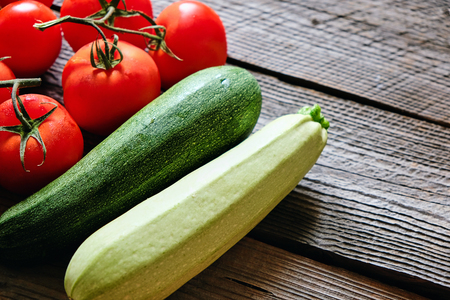 Zucchini and tomato on wood background copyspace