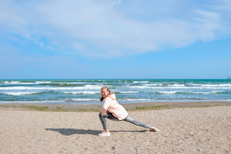 Young athletic girl makes gymnastic figures on the beach.
