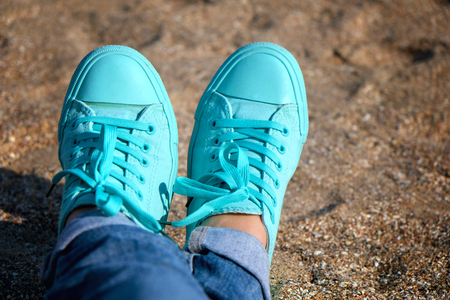 Concept with sneakers on bright sea sand. Sea summer vacation background.