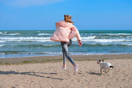 Happy young girl run with dog on beach.