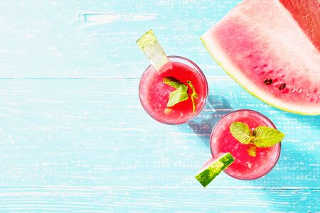 Watermelon summer cocktail with ice and mint leaves. Cold refreshment drink on blue wooden background with copy space.