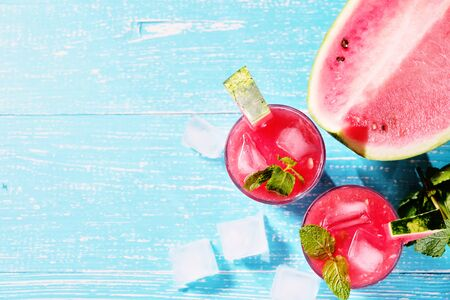 Watermelon summer cocktail with ice and mint leaves. Cold refreshment organic non-alcohol drink on blue wooden background with copy space.