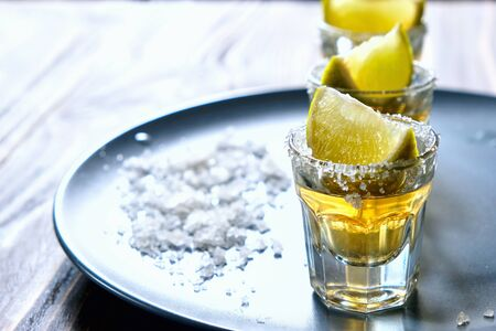 Tequila shot with lime and sea salt on grey plate