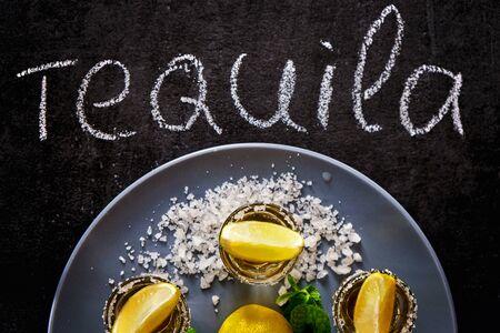 Gold tequila shot with lime, mint leaf and sea salt on grey plate. Reklamní fotografie