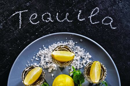 Gold tequila shot with lime and sea salt on grey plate.