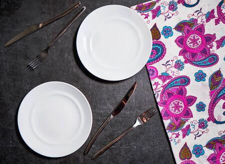 White plate, cutlery and napkin on stone table. Table setting.