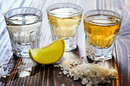 Mexican gold and silver tequila and lime salt on wood background