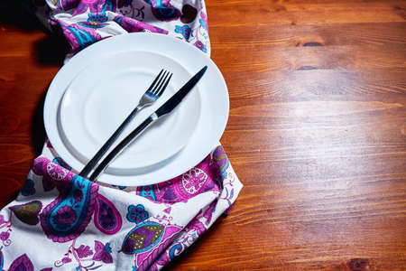 White plate, cutlery and napkin on wooden table. Table setting.
