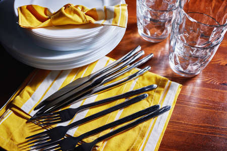 Tableware and decorations for serving a festive table. Plates, wine glasses and cutlery with decorative textile