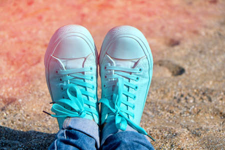 Concept with sneakers on bright sea sand. Sea summer vacation background with space for the text Reklamní fotografie