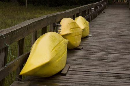 oceana: 3 yellow kayaks tied to a pier