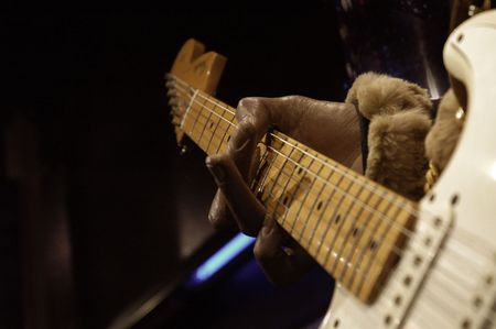 chord: Hand of a left handed guitar player holding a chord Stock Photo