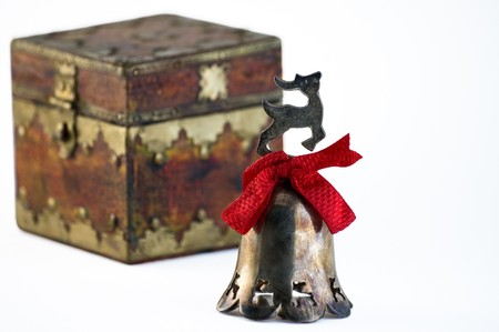 closed ribbon: a tarnished Christmas bell with a red ribbon in front of a treasure chest