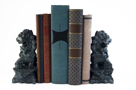 two carved marble lion bookends supporting a few books Stock Photo