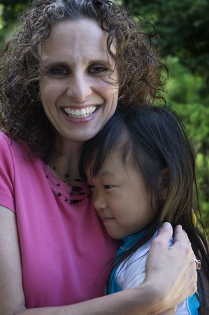 adopted: Proud mother hugging her adopted Chinese daughter
