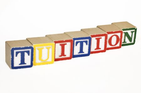 Wooden blocks laid out horizontally spelling out tuition