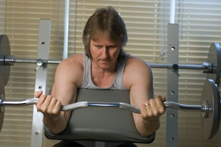 middle aged man doing repetitive exercised with weights photo