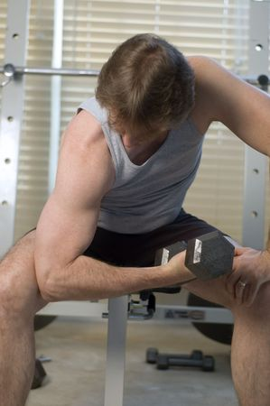 Middle aged man working his biceps curling weights photo