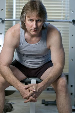 middle aged man sitting on the bench after his workout photo