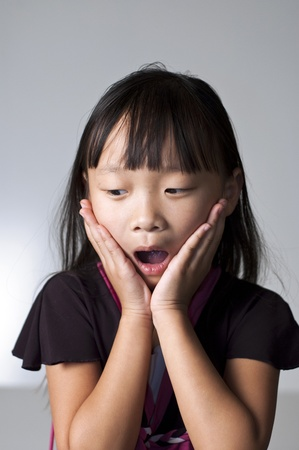 Pretty Asian girl with her hands to her face in shock Stock Photo