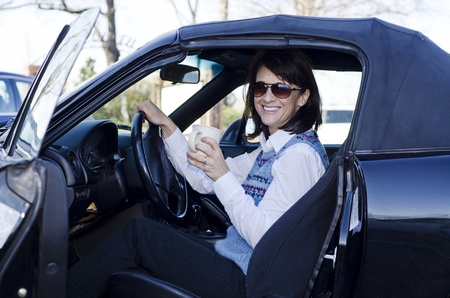 woman in her car drinking a cup of coffee