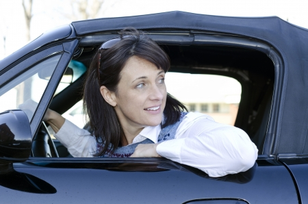 backward: Pretty woman looking behind her as she backs up her car Stock Photo