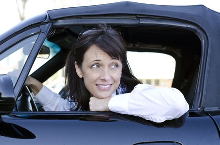 woman looking back as she sits stuck in traffic photo