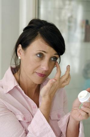 arrugas: Mujer bonita aplicación de crema hidratante para el rostro