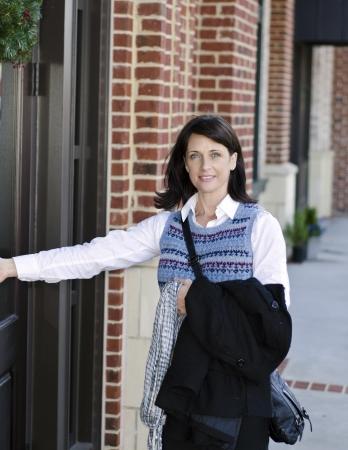 abriendo puerta: Mujer bonita de abrir una puerta a un edificio de oficinas Foto de archivo