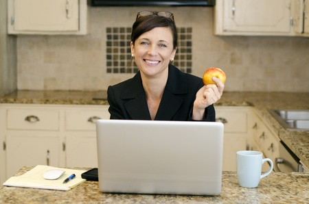 Working mom with makeshift office set up in th ekitchen photo