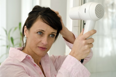 hairdryer: Pretty woman styling her hair as she prepares for her day Stock Photo