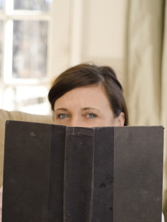 Blurred woman reading a focused and mysterious book photo