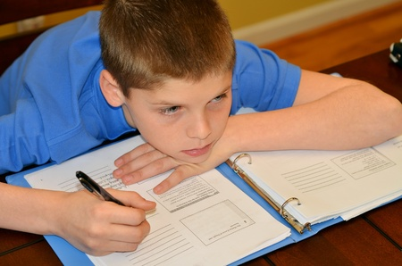 Young boy drifts from his concentration while studying Foto de archivo