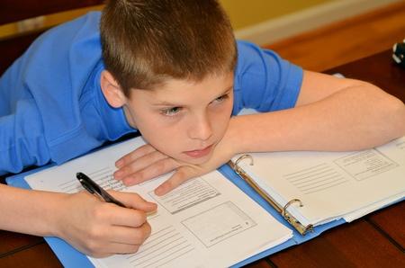 deberes: Chico joven se desv�a de su concentraci�n mientras estudia