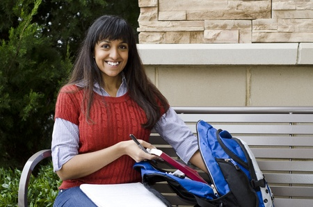 bookbag: Happy Middle-eastern student reaching into her book bag