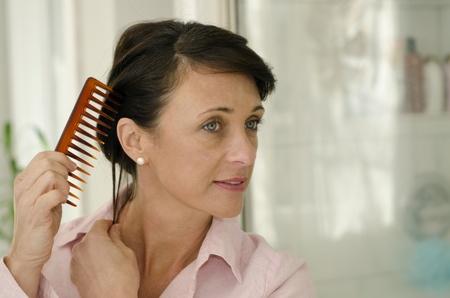 Pretty woman fissa i capelli con un pettine a denti di grandi dimensioni