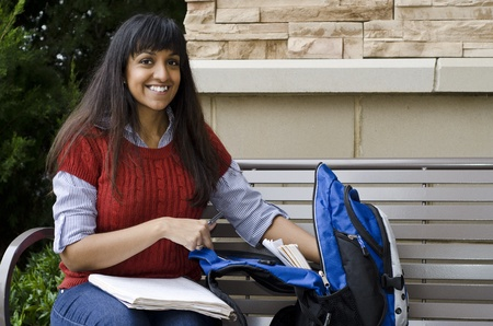 middle eastern clothes: Busy student reaching into her bookbag for something Stock Photo