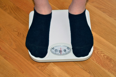 Young man standing on a scale getting his weight photo