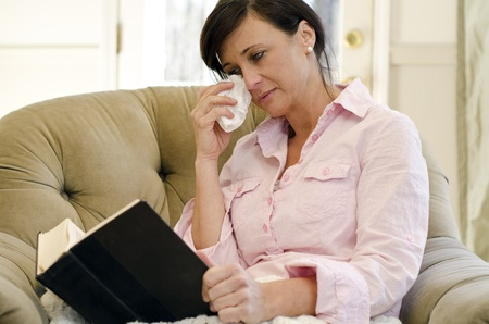 Woman curled up in a chair reading a book Stock Photo
