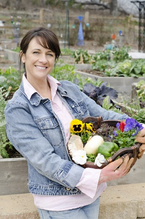 pansies: Attractive gardener with a basket full of flowers and produce