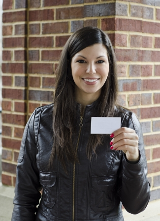 Beautiful woman in black leather offering her card photo
