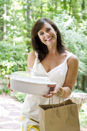 Pretty woman bringing a covered dish to a neighbor Stockfoto