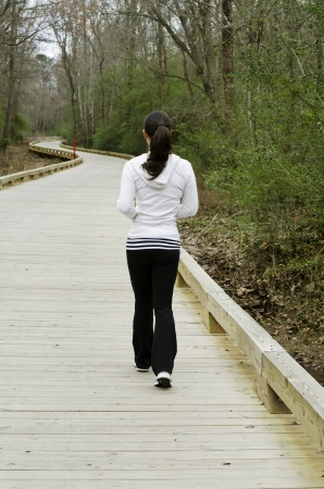 Fit and attractive young lady jogging on a walkway