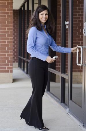 abriendo puerta: Hermosas mujeres de negocios que regresan a su oficina Foto de archivo