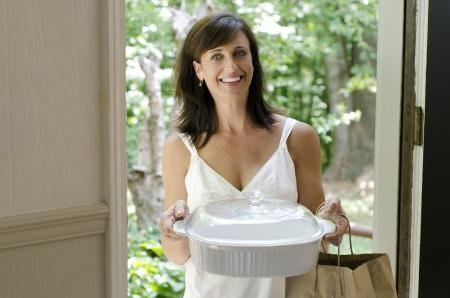 welcome party: Mujer bonita que visitar a un amigo y trayendo un plato cubierto