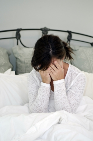 distraught woman upset and crying in bed photo