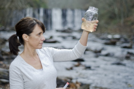 place of research: Female researcher checking the water quality from a river